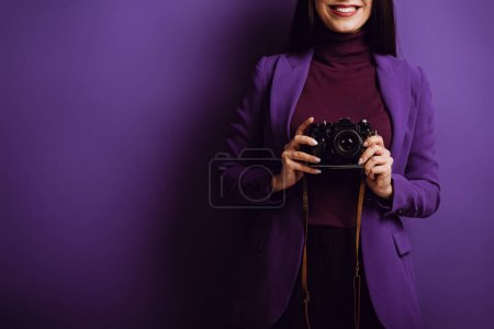 cropped view of smiling photographer holding digital camera on purple background