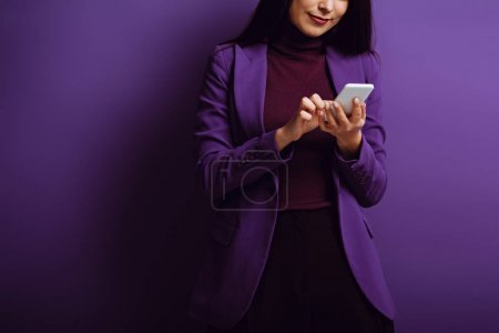 Photo for Cropped view of stylish woman typing on smartphone on purple background - Royalty Free Image