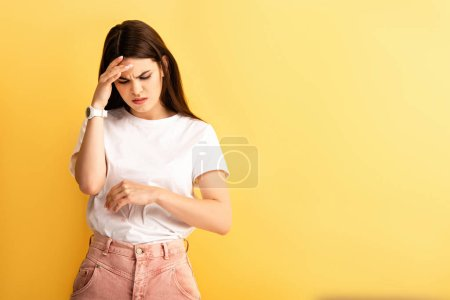 Photo for Exhausted, displeased girl touching head while suffering from headache isolated on yellow - Royalty Free Image