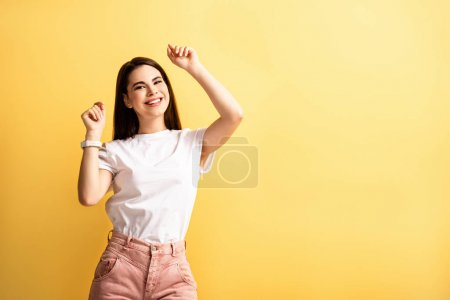 Photo pour Happy girl dancing with raised hands while smiling at camera isolated on yellow - image libre de droit
