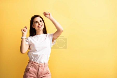 feliz chica bailando con las manos levantadas mientras sonríe a la cámara aislada en amarillo
