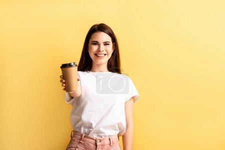 Photo pour Heureux attrayant fille montrant café pour aller tout en souriant à la caméra isolé sur jaune - image libre de droit
