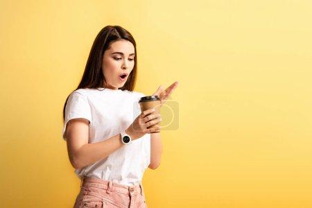 Photo pour Surprise fille debout avec la bouche ouverte en tenant le café pour aller isolé sur jaune - image libre de droit