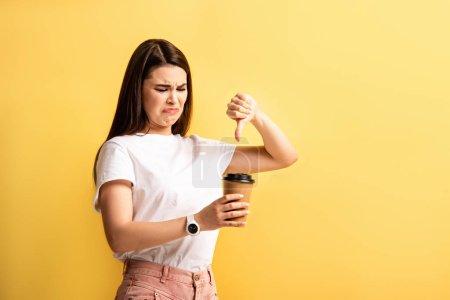 Photo pour Mécontent fille montrant pouce vers le bas tout en tenant café pour aller isolé sur jaune - image libre de droit