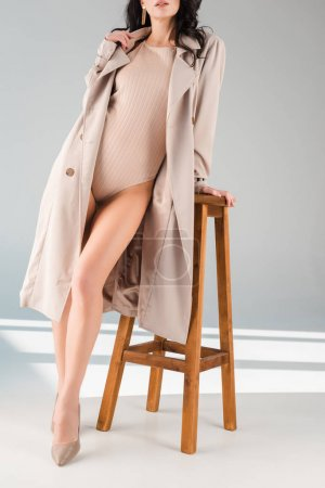 Photo for Cropped view of woman in bodysuit and coat standing near stool on grey background - Royalty Free Image