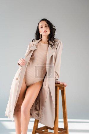 Photo pour Jolie femme en body et manteau debout près de tabouret en bois sur fond gris - image libre de droit