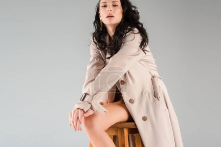 Photo pour Jolie femme en manteau regardant caméra isolée sur gris - image libre de droit