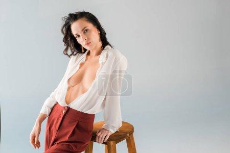 Photo pour Attrayant et sexy femme en chemise et pantalon regardant caméra isolé sur gris - image libre de droit