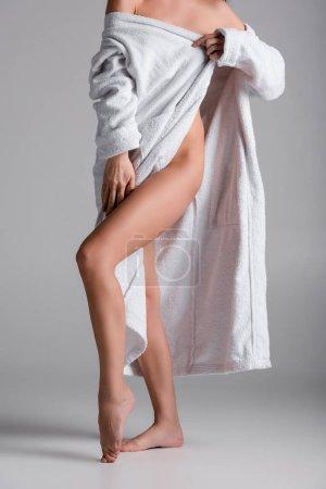 Photo pour Vue recadrée de femme sexy en peignoir sur fond gris - image libre de droit