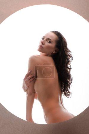 Photo pour Femme sexy et nue regardant la caméra isolée sur blanc en cercle - image libre de droit