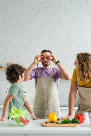 Photo for Bearded homosexual man covering eyes with cherry tomatoes near mixed race son and partner - Royalty Free Image