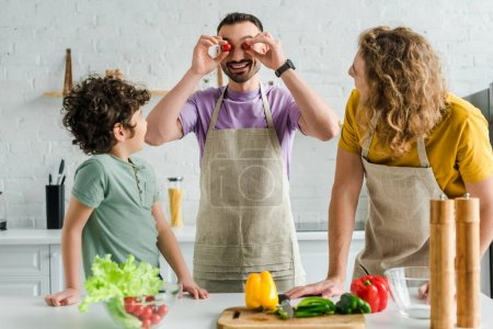 Photo for Happy and bearded homosexual man covering eyes with cherry tomatoes near mixed race son and partner - Royalty Free Image