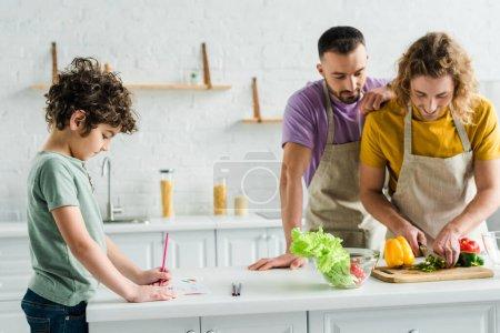 Photo pour Homosexuels cuisinant près d'une race mixte fils dessinant avec un crayon de couleur - image libre de droit