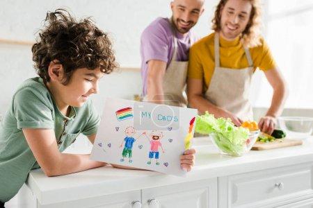 Photo pour Foyer sélectif d'enfant métis tenant l'image avec mes papas lettrage près heureux parents homosexuels - image libre de droit
