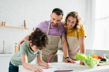 Photo for Happy homosexual parents looking at mixed race kid drawing picture - Royalty Free Image