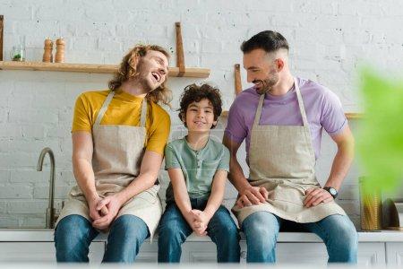 Photo pour L'orientation sélective de parents homosexuels heureux souriant avec un fils de race mixte - image libre de droit