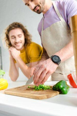 Photo pour Focus sélectif de l'homme homosexuel barbu cuisiner près de son partenaire à la maison - image libre de droit