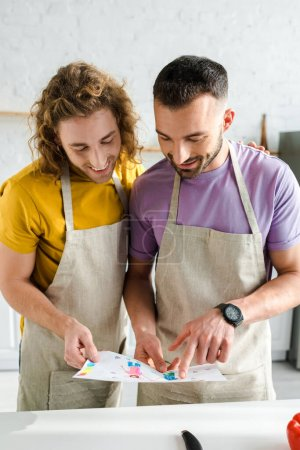 Photo for Happy homosexual men looking at colorful drawing - Royalty Free Image