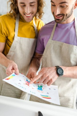 Photo for Happy homosexual men looking at colorful drawing with my dads lettering - Royalty Free Image