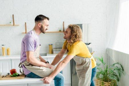 Photo pour Profile of happy homosexual men looking at each other - image libre de droit