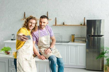 Photo pour Foyer sélectif des hommes homosexuels heureux dans les tabliers prenant selfie dans la cuisine - image libre de droit