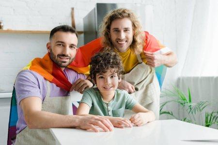 szczęśliwy homoseksualista mężczyźni z tęcza lgbt flaga w pobliżu wesoły mieszane rasy syn