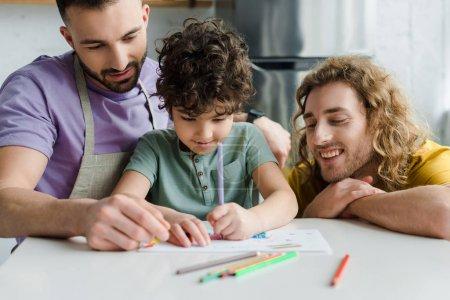Photo pour Selective focus of mixed race kid drawing near happy homosexual parents - image libre de droit