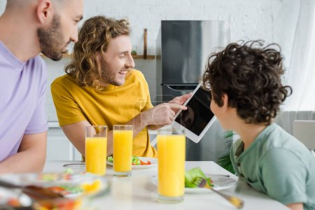 Photo for Happy homosexual man pointing with finger at digital tablet with blank screen near mixed race son - Royalty Free Image