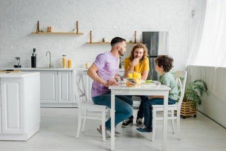 Photo pour Des parents homosexuels et un fils métis mignon déjeunant à la maison - image libre de droit