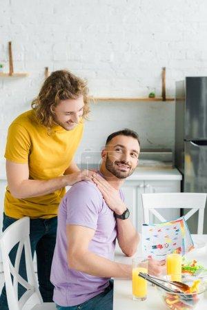 Photo pour Hommes homosexuels heureux tenant la main près de la salade et des verres avec du jus d'orange - image libre de droit