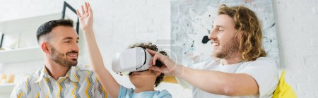 Photo for Panoramic shot of happy homosexual parents near mixed race son in virtual reality headset - Royalty Free Image