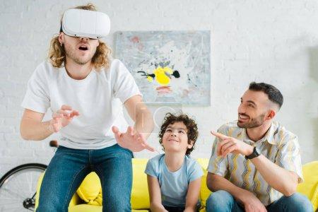 Photo pour Mignonne métisse enfant près d'un père homosexuel pointant du doigt son partenaire dans un casque d'écoute de réalité virtuelle - image libre de droit