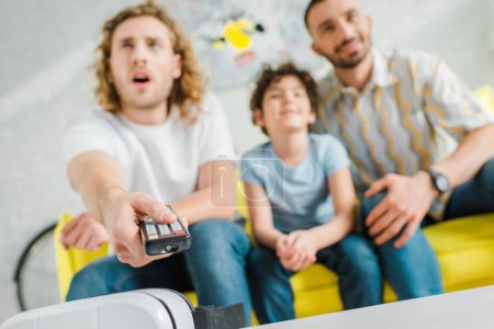 Photo pour Focalisation sélective des parents homosexuels et métis surveillance des enfants TV - image libre de droit