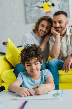 Photo pour Selective focus of happy mixed race kid drawing near homosexual parents - image libre de droit