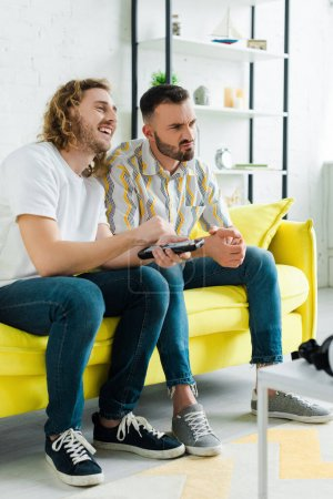 Photo pour Émotionnel homosexuel hommes regardant la télévision dans le salon - image libre de droit