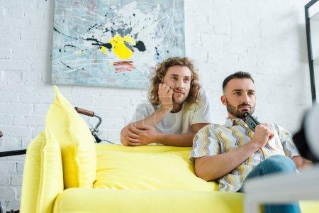 Photo pour Focalisation sélective des hommes homosexuels ennuyés qui regardent des films dans le salon - image libre de droit