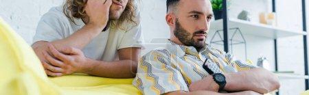 Photo pour Photo panoramique d'homosexuels mécontents regardant un film dans un salon - image libre de droit