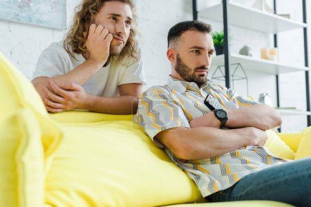 Photo pour Focalisation sélective des hommes homosexuels mécontents qui regardent des films dans le salon - image libre de droit