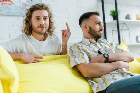 selective focus of displeased homosexual man showing middle finger to partner while watching movie in living room