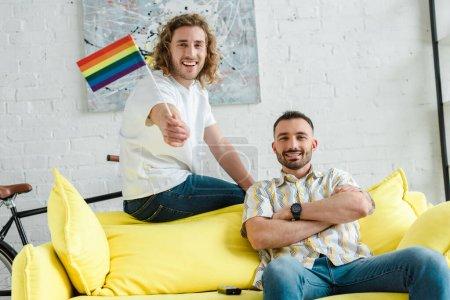 Foto de Los hombres homosexuales alegres sonriendo cerca de la bandera de lgbt en el salón. - Imagen libre de derechos