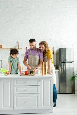 Foto de Hombres homosexuales cocinando cerca de un lindo hijo de raza mixta - Imagen libre de derechos