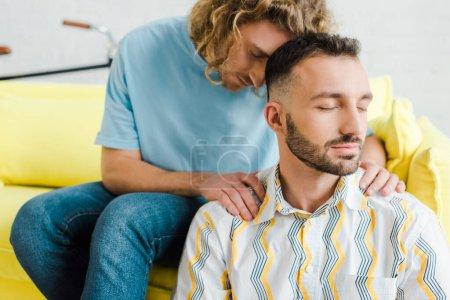 Photo pour Beaux hommes homosexuels avec les yeux fermés assis dans le salon - image libre de droit