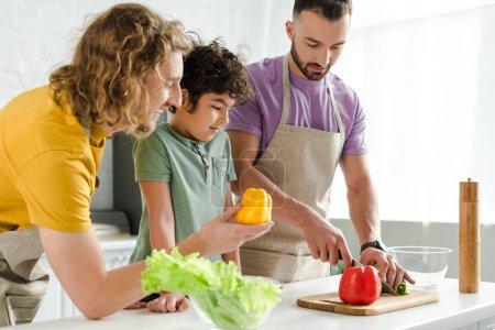 Photo pour Curly mixed race enfant près de parents homosexuels heureux dans la cuisine - image libre de droit