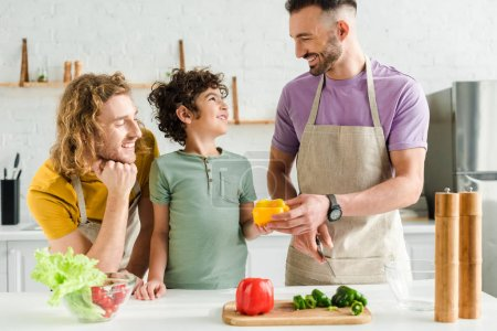 Photo for Curly mixed race kid near happy homosexual parents in kitchen - Royalty Free Image