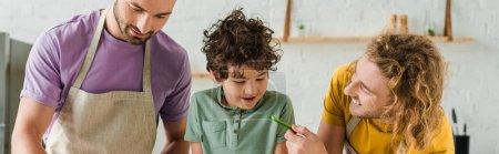 panoramiczne ujęcie słodkie mieszane rasy dziecko patrząc na homoseksualnego ojca z plasterkami papryki