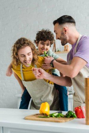 brodaty homoseksualny ojciec karmienie mieszane rasy syn z papryka w pobliżu partnera