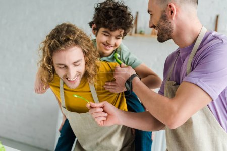 Photo pour Happy homosexual father holding bell poper near partner and mixed race son - image libre de droit