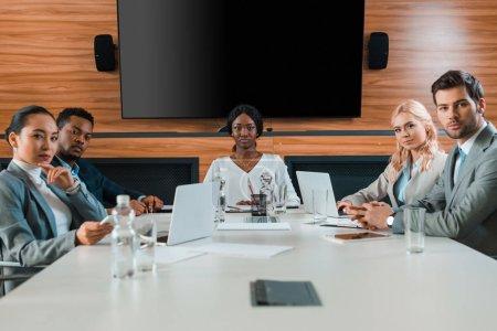 Photo pour De jeunes entrepreneurs multiculturels confiants assis dans une salle de conférence avec un écran de disque compact sur le mur - image libre de droit