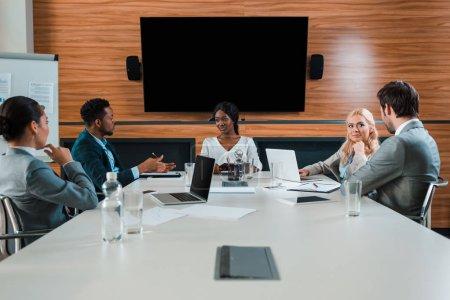 Photo pour De jeunes gens d'affaires multiculturels parlant pendant une réunion dans une salle de conférence avec un écran de disque compact au mur - image libre de droit