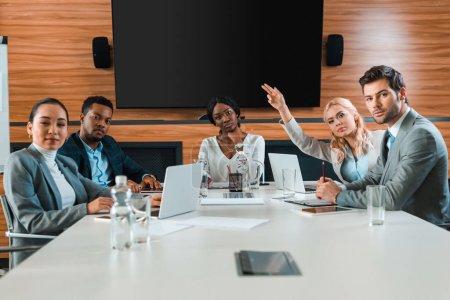 Photo pour Jeune femme d'affaires levant la main alors qu'elle était assise dans la salle de conférence près de collègues multiculturels regardant la caméra - image libre de droit